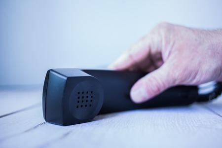 Männliche hat greift nach einem schwarzen Telefonhörer. Stock Photo