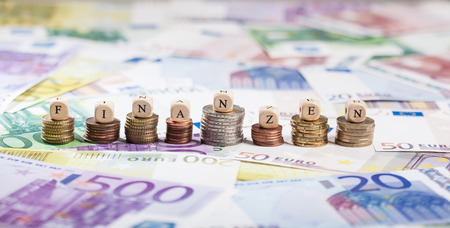 finanzen: Cube letters building the term Finanzen (finance) in German. Shallow depth of field, focus on coin stacks and letters. Stock Photo