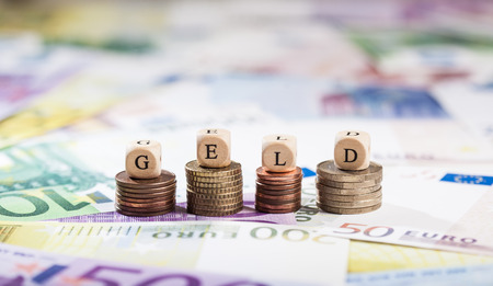 geld: Cube letters building the term Geld (German for money). Shallow depth of field, focus on coin stacks and letters.