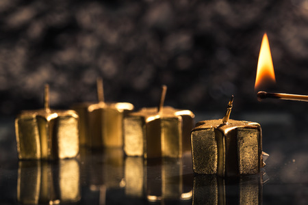 low key lighting: Lighting the first of four golden advent candles, on a dark black slate underground, low key lighting, shallow depth of field. Stock Photo