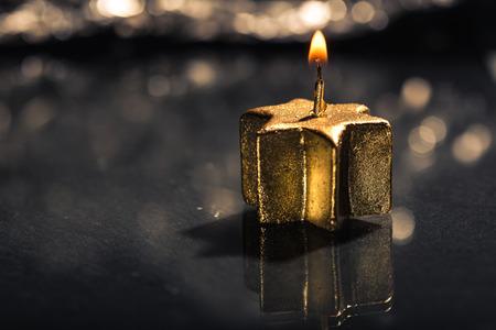 low key lighting: Lit golden advent candle, on a dark black slate underground, low key lighting, shallow depth of field.