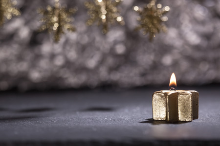 low key lighting: Lit golden advent candle, on a dark black slate underground, low key lighting, shallow depth of field, with star ornaments on top.