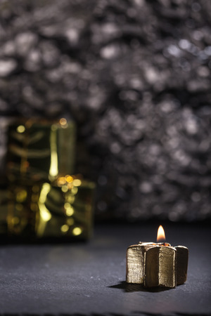 low key lighting: Lit golden advent candle, on a dark black slate underground, low key lighting, shallow depth of field with glitter and gift boxes in background. Stock Photo