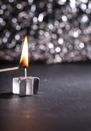 lit image: Silver candle lit with a match on black background, bokeh lights and shallow depth of field, vertical image. Stock Photo