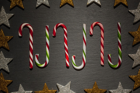 golden border: Many striped candy canes on dark slate background with frame of golden and silver stars, Christmas decoration.