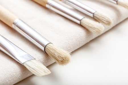 Set of paint brushes in different sizes, in carry bag textile, isolated on white background. Shallow depth of field, focus on large round brush on the left. Stock Photo
