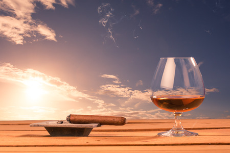 indulgence: Symbolic success or indulgence, cognac glass in front of sunset sky on wood table.