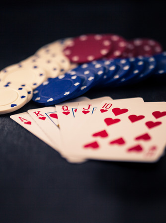 olden day: Cards with royal flush in hearts, poker chips, retro color look with split toning, dark slate surface as underground.