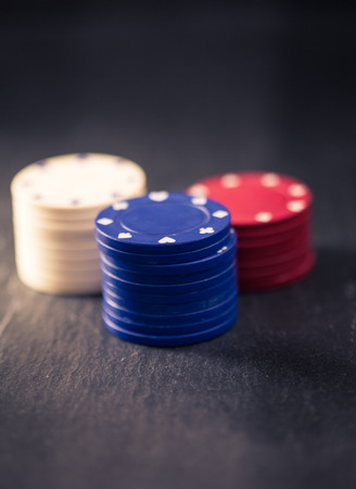 olden day: Stacks of blue, white and red poker chips, retro color look with split toning, dark slate surface as underground, shallow depth of field.