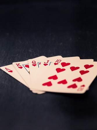 royal flush: Cards with royal flush in hearts, retro color look with split toning, dark slate surface as underground.