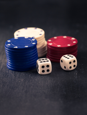 olden day: Two dices, poker chips in red, blue and white, retro color look with split toning, dark slate surface as underground, shallow depth of field.