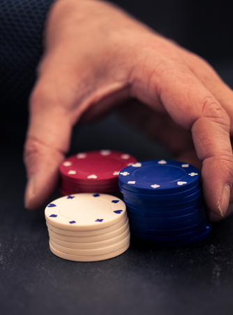olden day: Hand moving stacks of poker chips, going all in, retro color look with split toning, dark slate surface as underground.