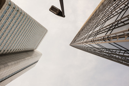 dreary: Looking up view of sharp angles on tall buildings in downtown Frankfurt Germany under overcast sky Stock Photo