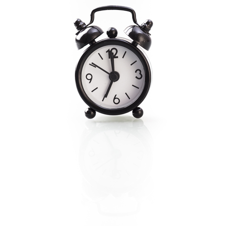 seven o'clock: Retro style alarm clock showing seven oclock, isolated on white background with reflection.