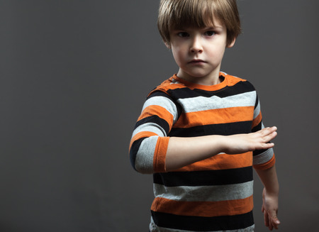 cool people: Cool  Preschooler  pretending to Fight in orange black striped shirt Stock Photo