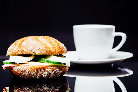 bread roll: Breakfast sandwich and cup of coffee, wholegrain bread roll with cucumber, ham and egg, chees, on black background with reflection.