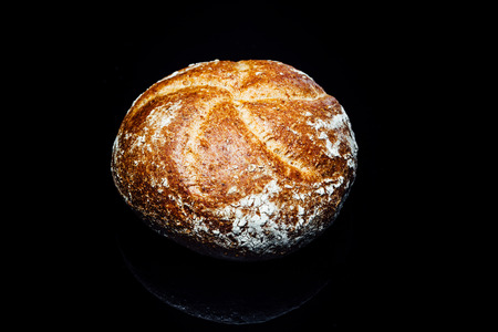bread roll: Top view closeup on wholemeal or wholegrain bread roll, isolated on black background with reflection.