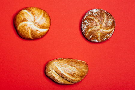 high angle view: High angle view on three different bread rolls on red background. Stock Photo