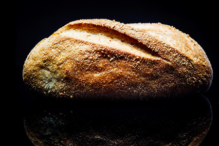 bread roll: Side view closeup on potato bread roll, isolated on black background with reflection. Stock Photo
