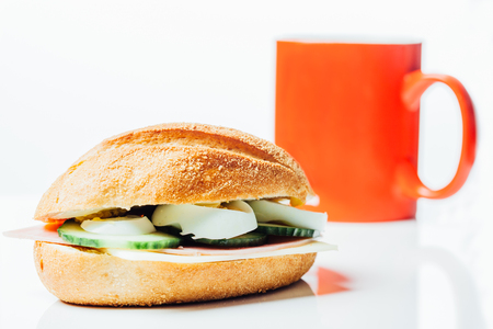bread roll: Breakfast sandwich and red coffee mug, potato bread roll with cucumber, ham and egg, chees, on white background with reflection.
