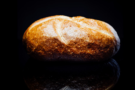 bread roll: Side view closeup on bread roll, isolated on black background with reflection.