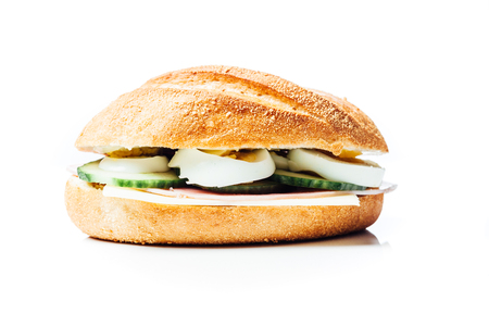 bread roll: Breakfast sandwich, potato bread roll with cucumber, ham and egg, chees, on white background with reflection. Stock Photo