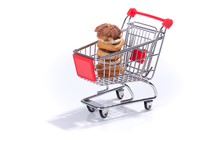 titbits: Shopping cart with cookies, isolated on white background