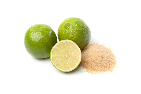 unprocessed: Two whole and one halved green limes, and raw sugar, isolated on white background.