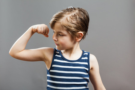 muscle shirt: Little Sportive Tough Boy in striped  muscle shirt, looking at his muscles