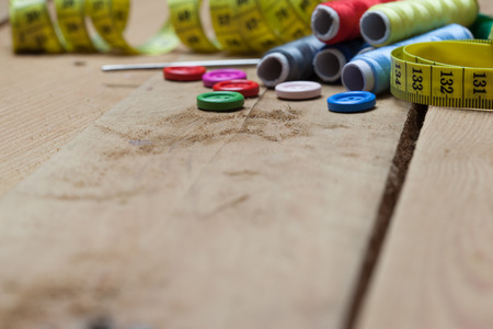 Set of tools with buttons, needle, thread spools for home made embroidery, needlework and tailoring, on wooden background.