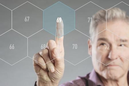 futuristic man: Senior man choosing retirement age on futuristic virtual digital screen