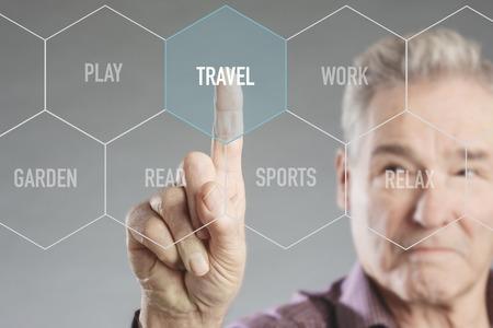 Senior man choosing on virtual digital screen between leisure activities and selects travel Stock Photo