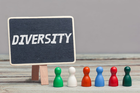 wood panelling: six differently colored, wooden board game pieces, standing in line on wood panelling, next to a blank copy space chalkboardblackboardsign. Grey background. work environment, concept image. Stock Photo