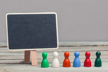 panelling: six differently colored, wooden board game pieces, standing in line on wood panelling, next to a blank copy space chalkboardblackboardsign. Grey background. work environment, concept image. Stock Photo