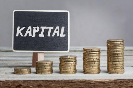 Kapital (Vermögenswerte) in deutscher Sprache, weiße Kreideart auf schwarzem Brett, Eurogeldmünzenstapel des Wachstums auf hölzernem Tisch.