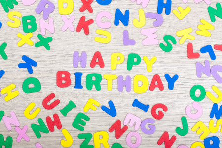 and spelling: A cluster of colored letters on wooden table spelling happy birthday. studioshot.