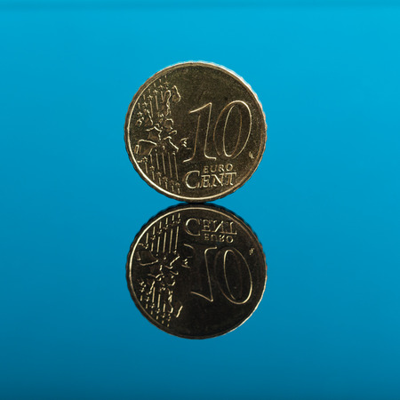 cents: 10 cents, Euro money coin on blue colored background with reflection on mirror surface, studio shot. Stock Photo