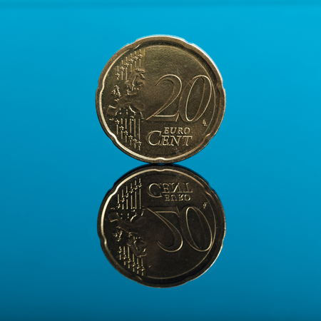 cents: 20 cents, Euro money coin on blue colored background with reflection on mirror surface, studio shot.