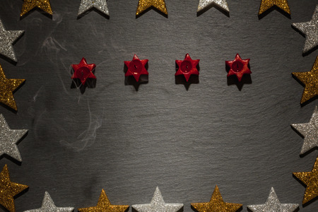 blown: Four candles blown out with smoke on slate background with frame of golden and silver stars, Christmas decoration.