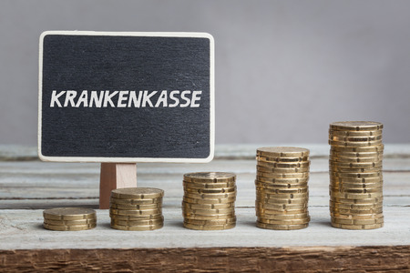 Krankenkasse (health insurance)  in German language, white chalk type on black board, Euro money coin stacks of growth on wood table.