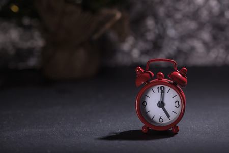 Red alarm clock set to 5 o'clock, Christmas decoration and present gift boxes in background, shallow depth of field