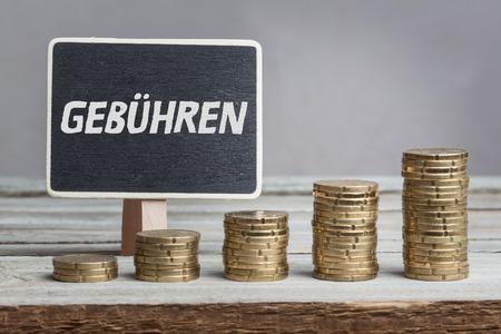 Gebühren (tariffs) in German language, white chalk type on black board, Euro money coin stacks of growth on wood table. 写真素材