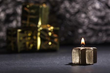 Lit golden advent candle, on a dark black slate underground, low key lighting, shallow depth of field with glitter and gift boxes in background. 免版税图像