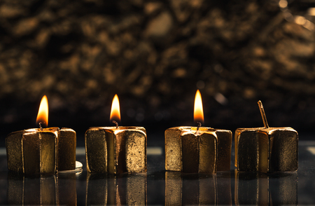 Three golden candles lit for third advent, shallow depth of field with reflection and bokeh light background.