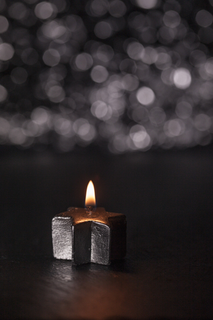 Lit silver candle on black background, bokeh lights and shallow depth of field, vertical image.