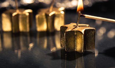 Lighting the first of four golden advent candles, on a dark black slate underground, low key lighting, shallow depth of field. Stok Fotoğraf