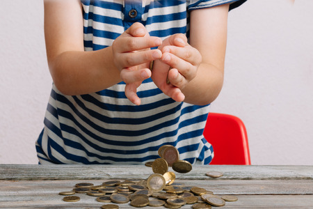 Boy dropping heap of coins on wood table.