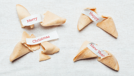 foretelling: Four fortune cookies with season greetings on table cloth