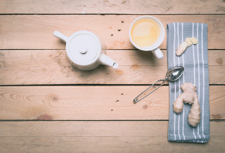 Ginger tea, with spoon and grey towel, high angle birds eye view on wood table.
