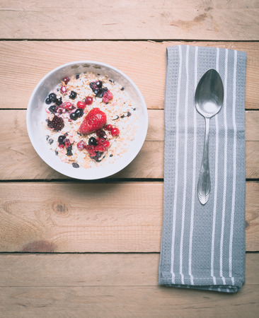 birds eye: Bowl of berry and grain cereal muesli with spoon and grey towel, high angle birds eye view on wood table. Stock Photo